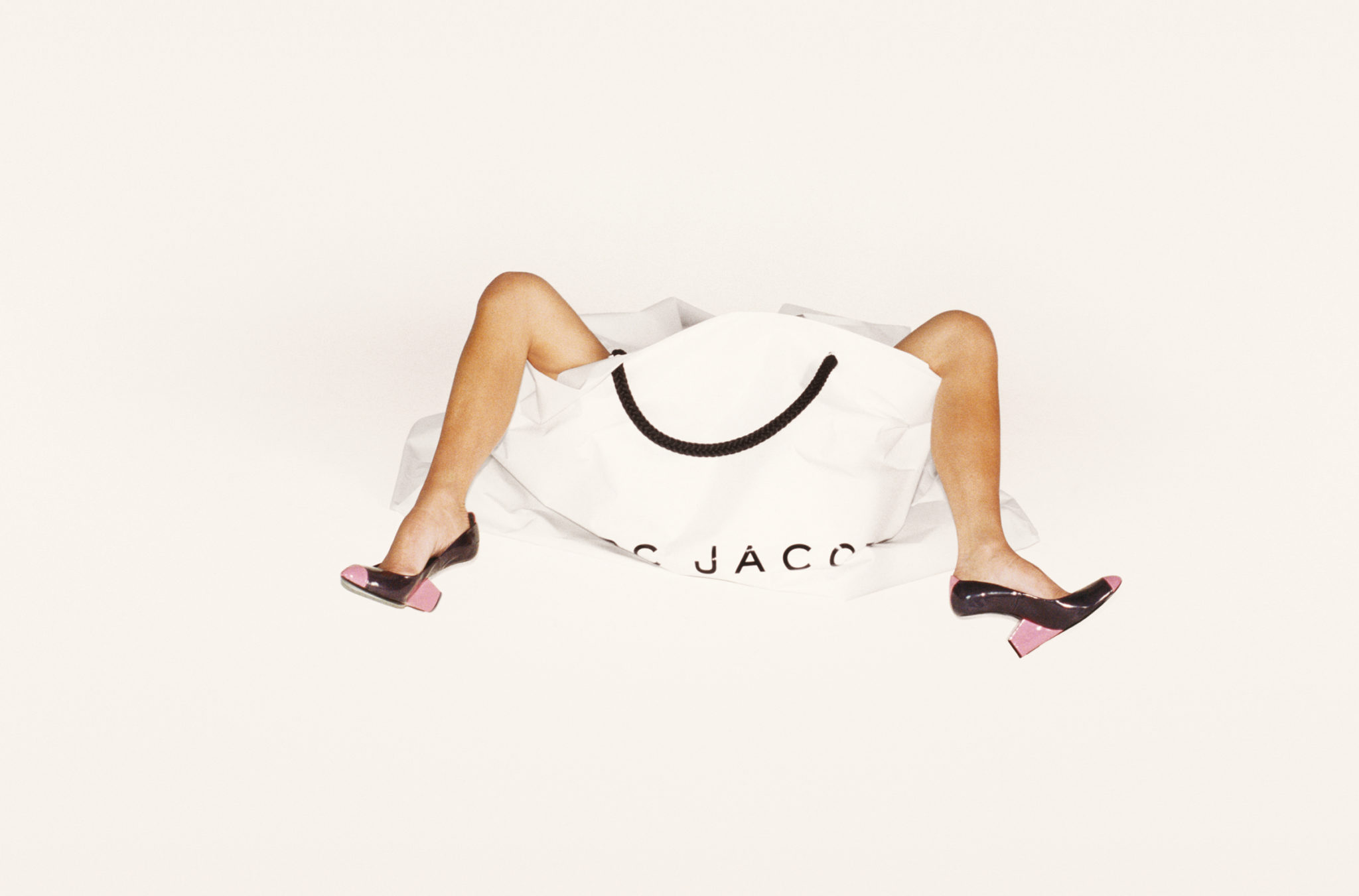 Fotografia utrzymana w jasnych, kremowych barwach. Na środku ustawiona jest biała, papierowa torba na zakupy z czarnymi uchwytami oraz czarnym napisem Marc Jacobs. Z torby wystają kobiece nogi ubrane jedynie w buty na obcasie.