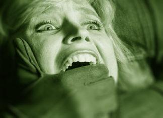 Wystraszona kobieta z ręką mężczyzny na ustach