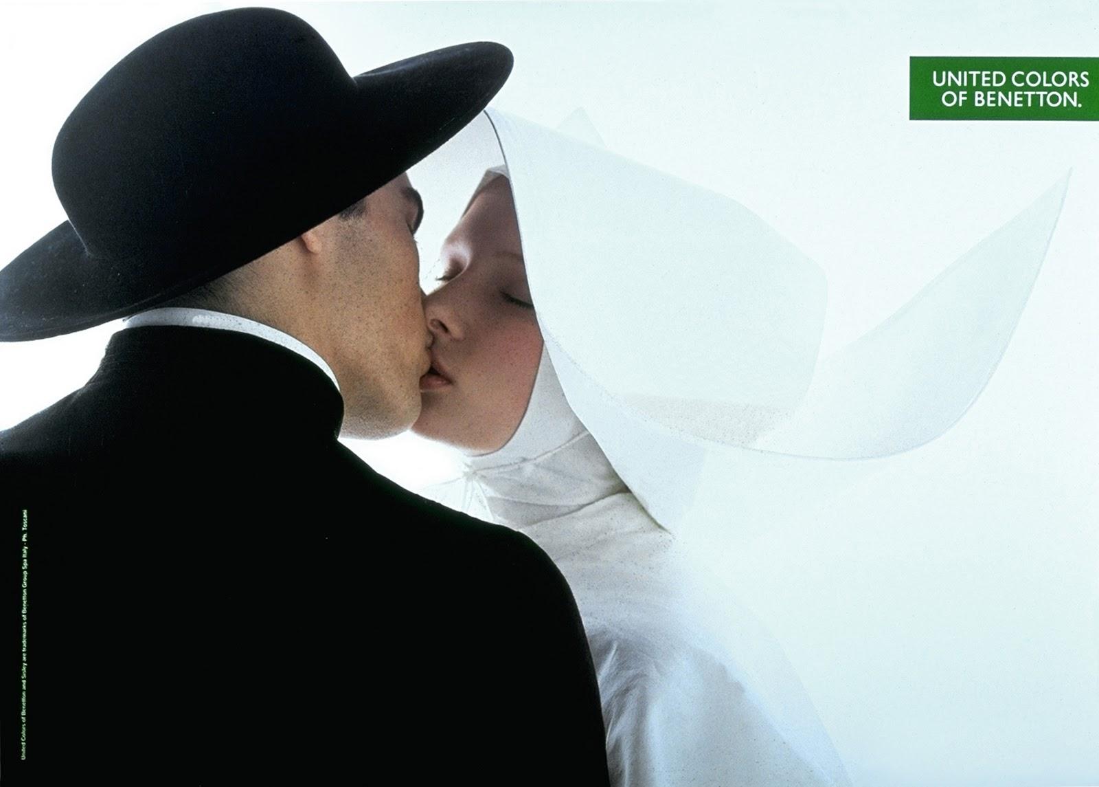 Fotografia kolorowa przedstawiająca zakonnicę całującą księdza. Po lewej stronie, zwrócony plecami do widza ksiądz, ubrany w czarną sutannę i czarny kapelusz. Po prawej stronie zakonnica w białym habicie i białym nakryciu głowy całuje mężczyznę. Zakonnica ma zamknięte oczy. W górnym prawym rogu znajduje się zielone logo z napisem United Colors of Benetton.