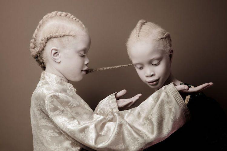 Dwie bliźniaczki stoją przodem do siebie, na przeciwko. Jedna ma podniesioną głowę i ręce, a druga patrzy się na jej dłonie.