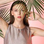 Dziewczyna, brunetka, stojąca na tle różowej ściany i liści palmy ubrana w brudno różową bluzkę pod szyję bez rękawów