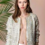 Dziewczyna, brunetka stojąca na tle różowej ściany i liści palmy ubrana w białą spódnicę i szarą marynarkę bez niczego pod spodem