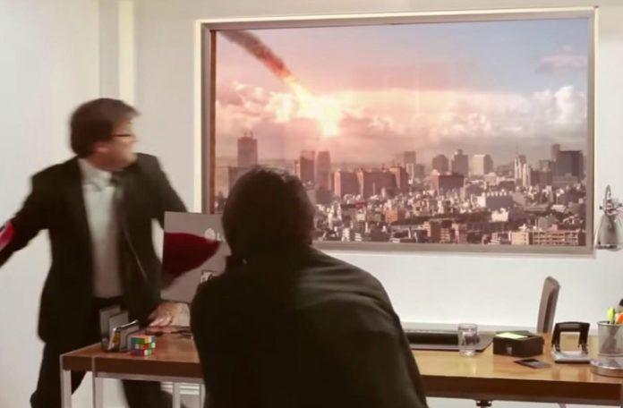 Mężczyzna uciekający zza biurka, na ścianie jest umieszczony telewizor imitujący okno, pokazujący jak na miasto spada kometa