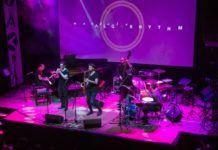 Zespół złożony z mężczyzn, stojący na scenie z różowym oświetleniem