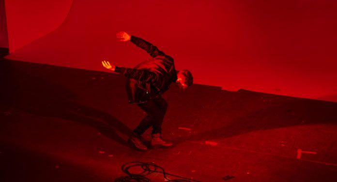 Pochylający się mężczyzna stojący w czerwonym świetle