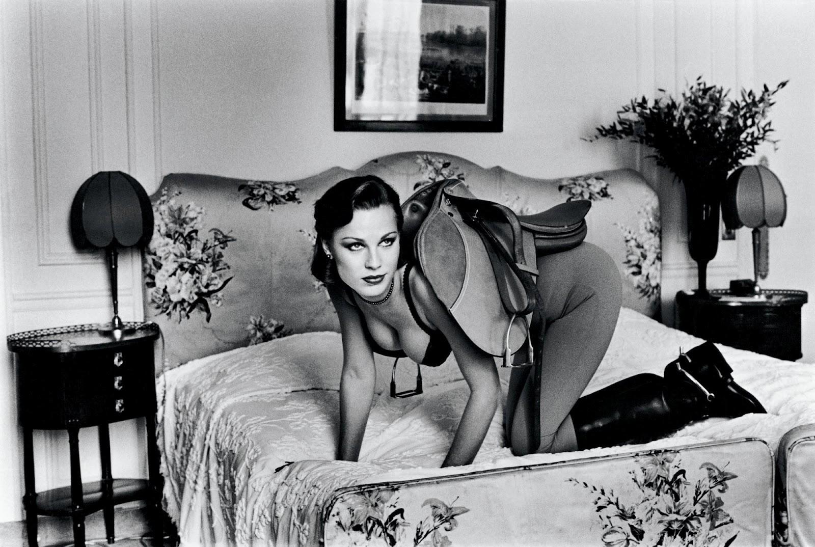 Zdjęcie czarno-białe. Kobieta klęcząca na łóżku, ubrana w czarny biustonosz, szare bryczesy oraz carne buty do jazdy konnej. Na jej plecach ułożono siodło.