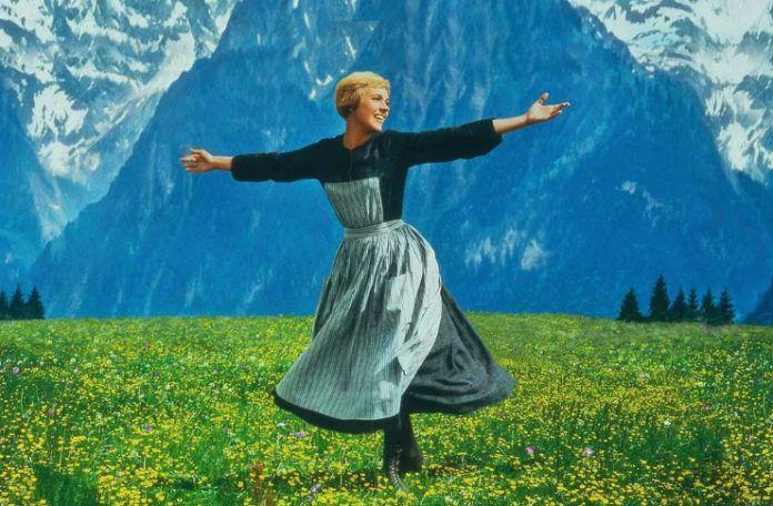 Kobieta ubrana w ludowy strój wykonująca obrót na łące, w tle góry