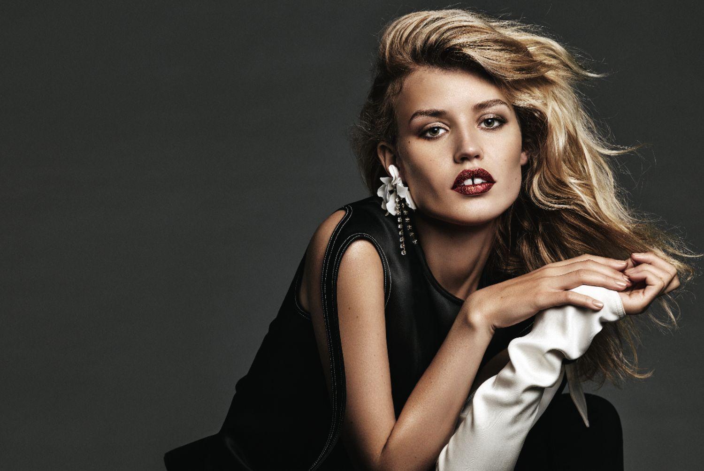 piekna blondynka z wielkimi ustami i szpara miedzy zebami pozuje na kresle od pasa w gore ma mocny makijaz i czarna sukienke