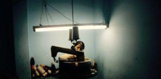 Zdjęcie kolorowe utrzymane w ciemnych barwach. Na środku, wśród przyrządów do obróbki tkanin siedzi kobieta. Zza maszyny ledwo widać połowę jej twarzy, drugą połowę przysłania ciemna grzywka.