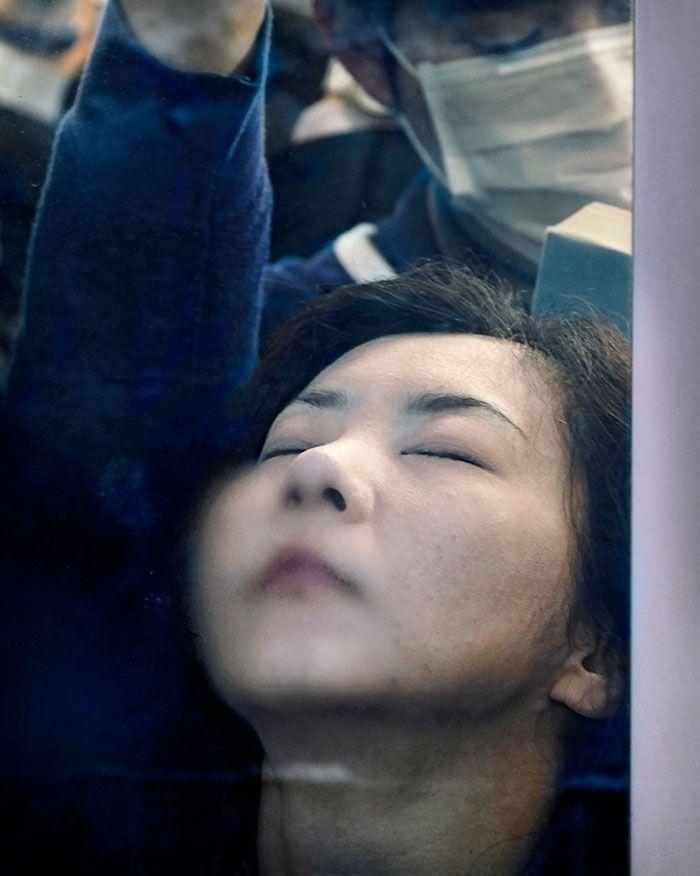 Kobieta z odchyloną głową i zamkniętymi oczami w zatłoczonym metrze