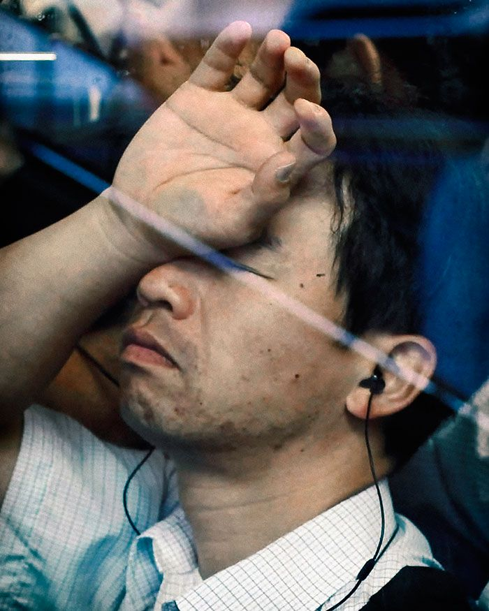 Mężczyzna siedzący w metrze, trzymający rękę na twarzy