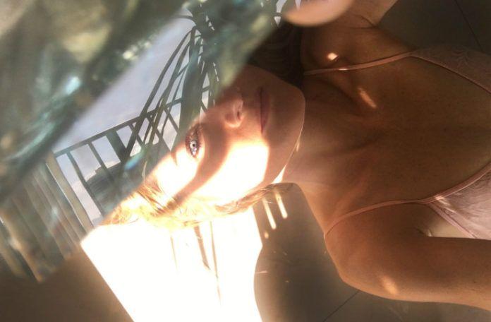 Portret dziewczyny, blondynki lezacej w polcieniu, zakrywajacej polowe twarzy lusterkiem