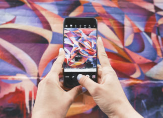 telefon w dloniach na kolorowym tle