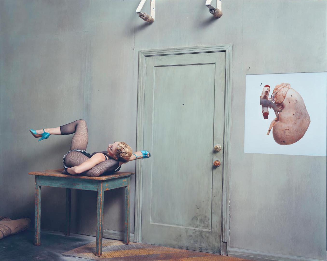 Zdjęcie kolorowe utrzymane w jasnych niebieskich kolorach. Po lewej stronie na obdrapanym niebieskim stole leży kobieta, blondynka w czarnym body i przezroczystych legginsach, na nogach ma turkusowe buty na obcasie, jej prawa noga uniesiona jest w górę i zgięta w kolanie, lewa noga założona jest za głowę. Po prawej stronie znajduje się ilustracja nerki