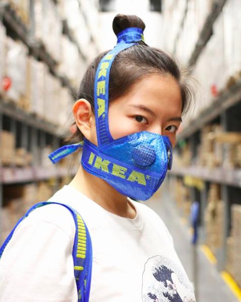 Azjatka stojaca w sklepie, ujecie portretowe boczne, na ustach ma zalozona niebieska maske ktora zakrywa jej kok z brazowych wlosow takze