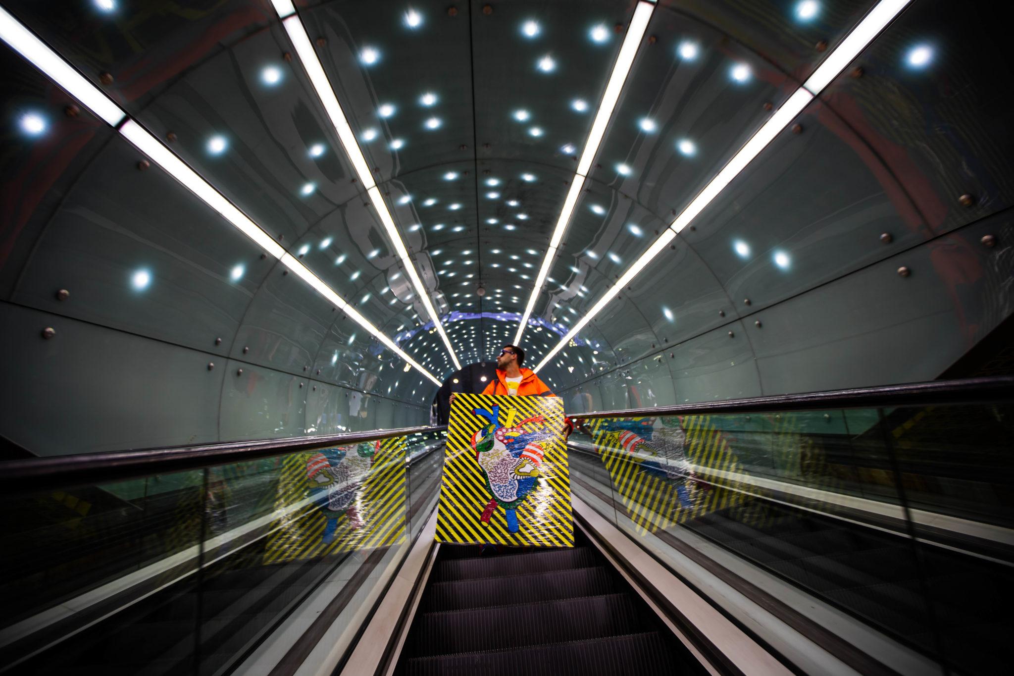 Mężczyzna na schodach w warszawkim metrze stoi z obrazem
