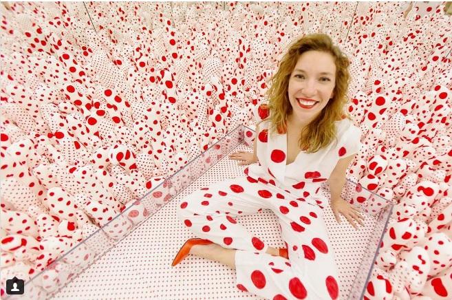 Zdjęcie przedstawia artystkę na tle tapety w czerwone groszki. Jej bluzka i spodnie są w takim samym wzorze.