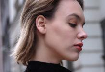 Blondwłosa dziewczyna z krótkimi włosami stojąca profilem