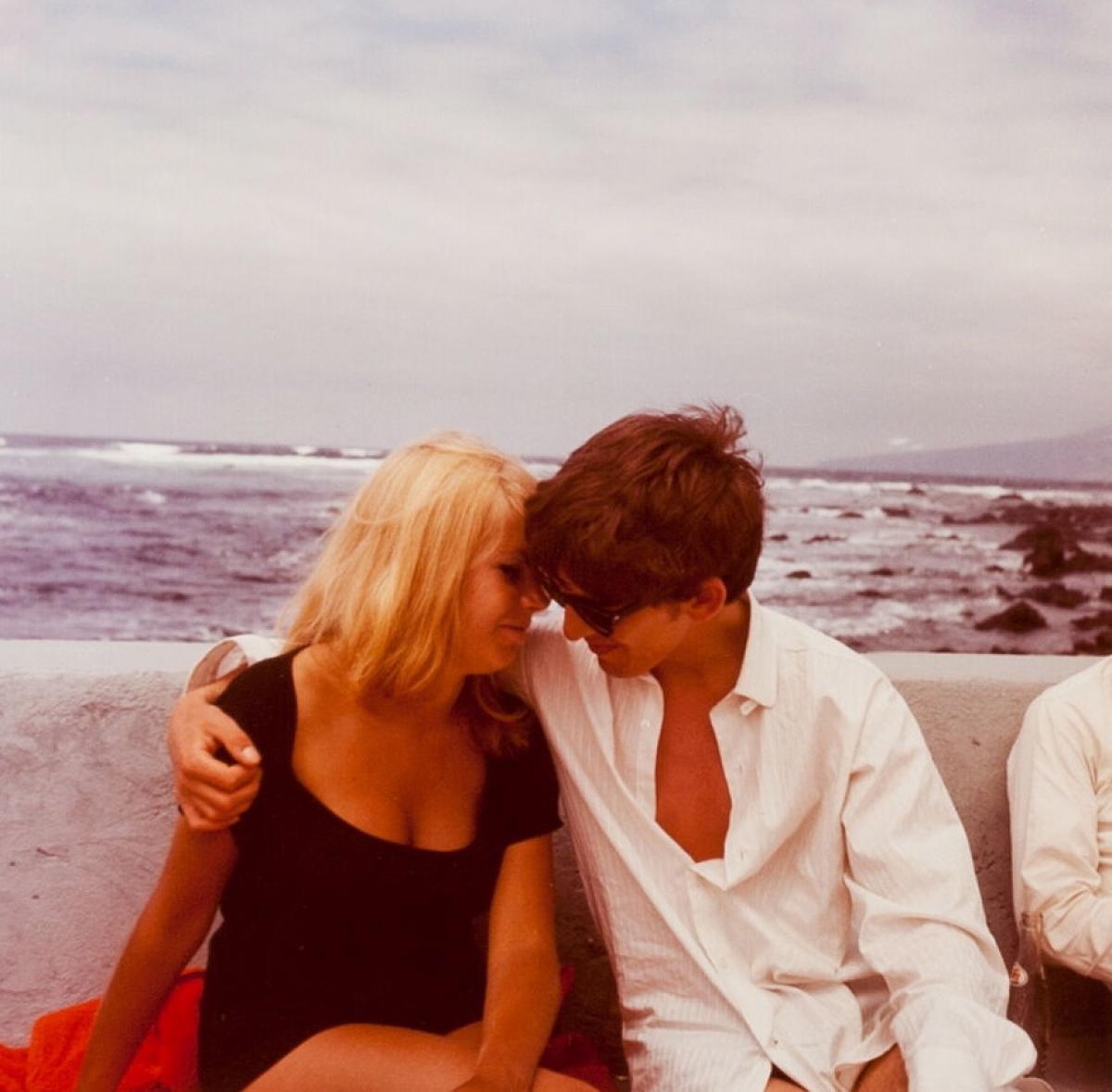 Na zdjęciu widzimy muzyka w białej koszuli i okularach przeciwsłonecznych obejmującego blondynkę w czarnej sukience. Oboje mają blisko siebie twarze i uśmiechają się.