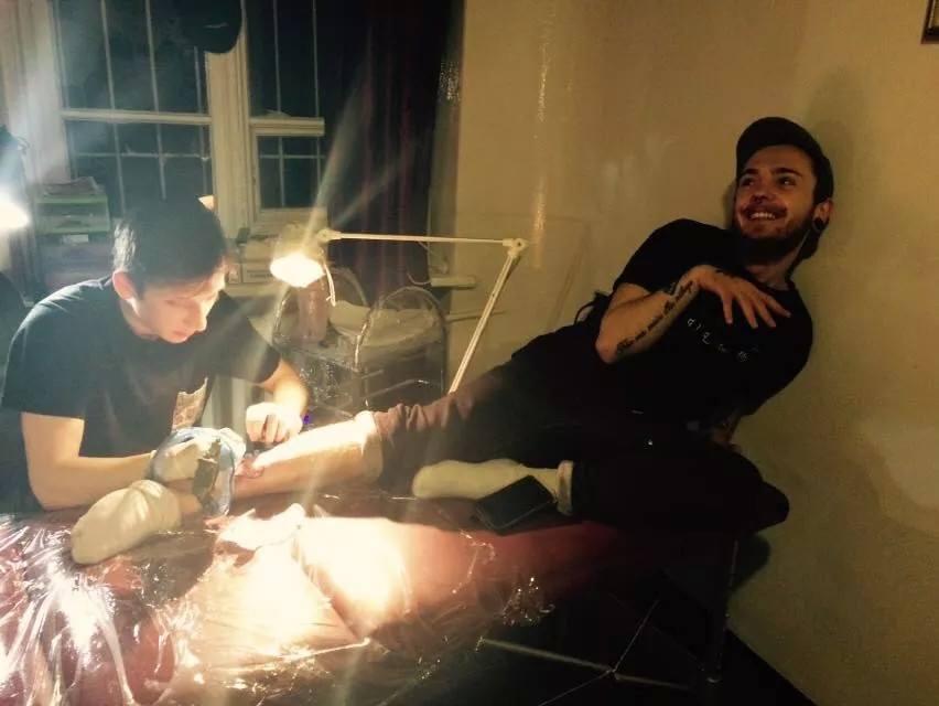 Na zdjęciu znajduje się dwóch mężczyzn. Jeden znajduje się w pozycji półsiedzącej na leżance. Drugi pochyla się nad jego nogą, wykonując tatuaż