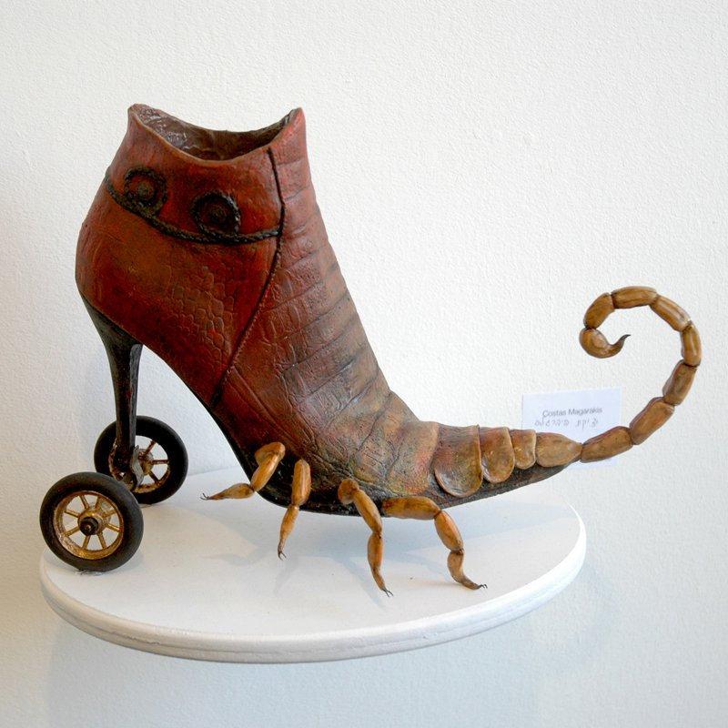 Rzeżba brązowego buta, którego obcas znajduję się na dwóch kółkach. Od śródstopia do palców odchodzą krętacze skorpiona.