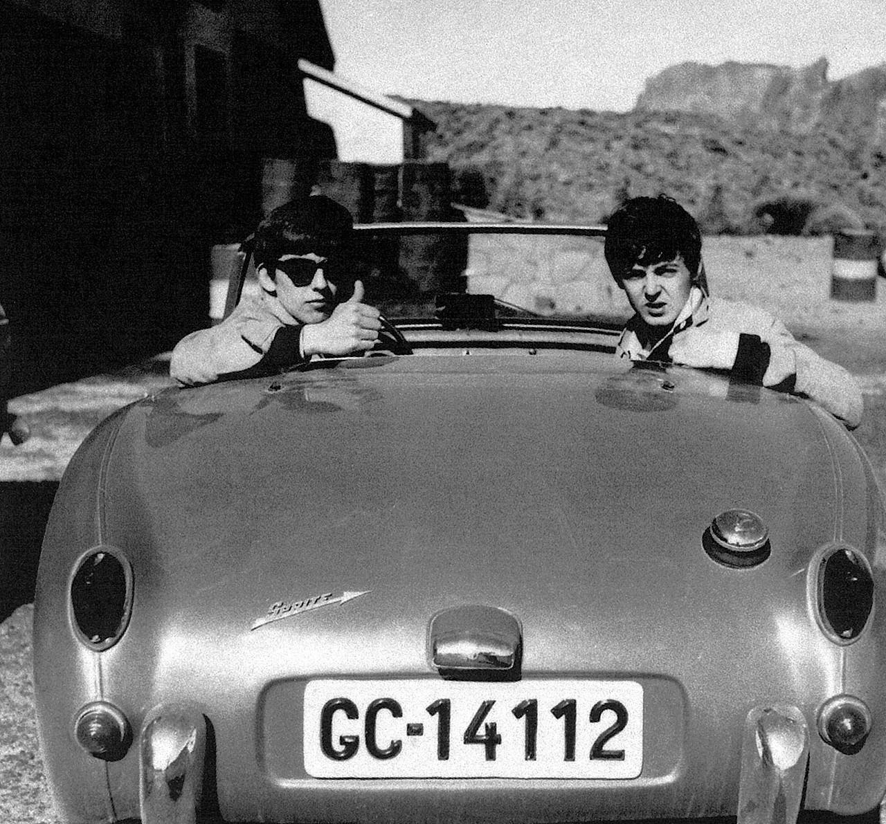Na zdjęciu widzimy dwóch muzyków, jeden w okularach przeciwsłonecznych. Siedzą w oldschoolowym kabriolecie.