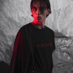 Zdjęcie chłopaka w czarnej koszulce z czerwonym światem odbijającym się od twarzy