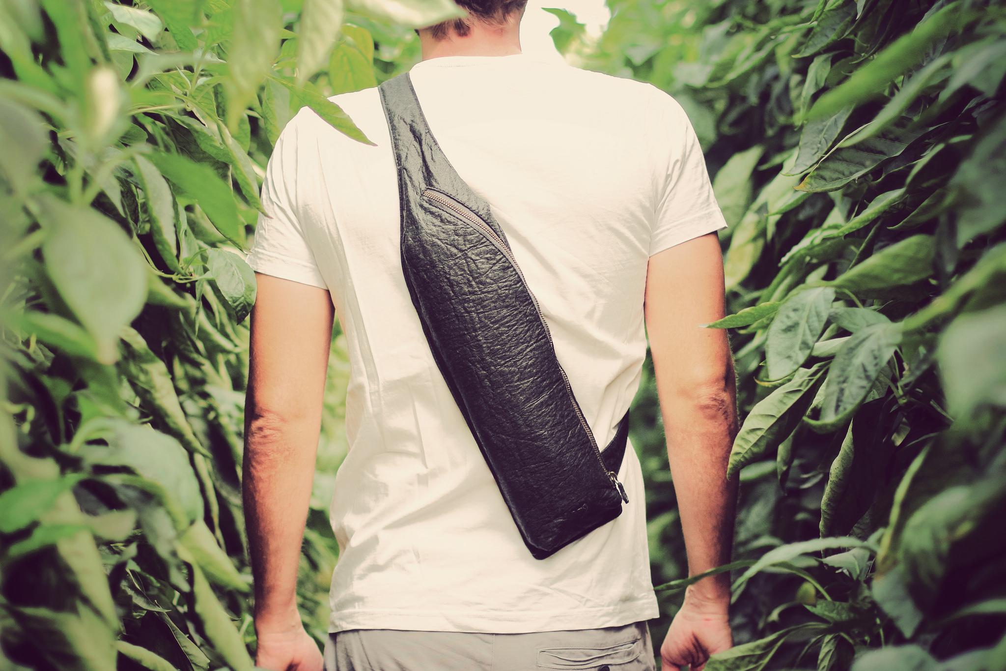 Mężczyzna stojący tyłem pośród zieleni w koszulce z krótkim rękawem i małym plecaku przełożonym przez ramę