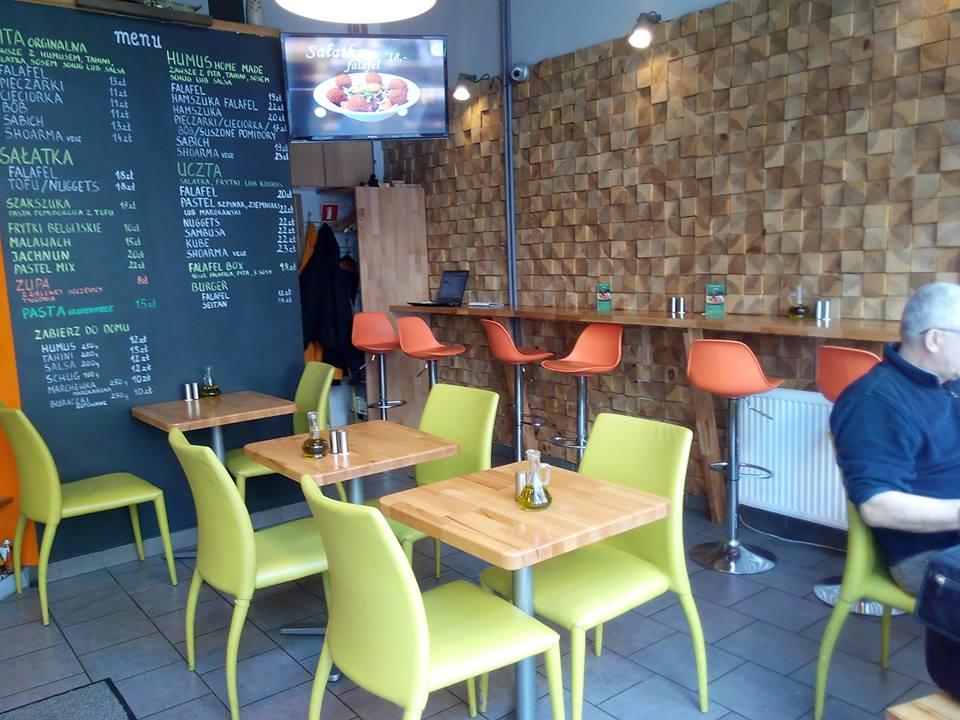 Zdjęcie wnętrza lokalu z brązowymi stolikami i kolorowymi krzesłami