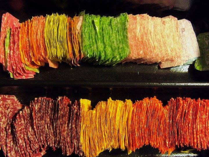 N zdjęciu widać posegregowane kolorystycznie papierki po cukierkach, dodatkowo wyprasowane, aby były one proste, bez żadnych zagięć.