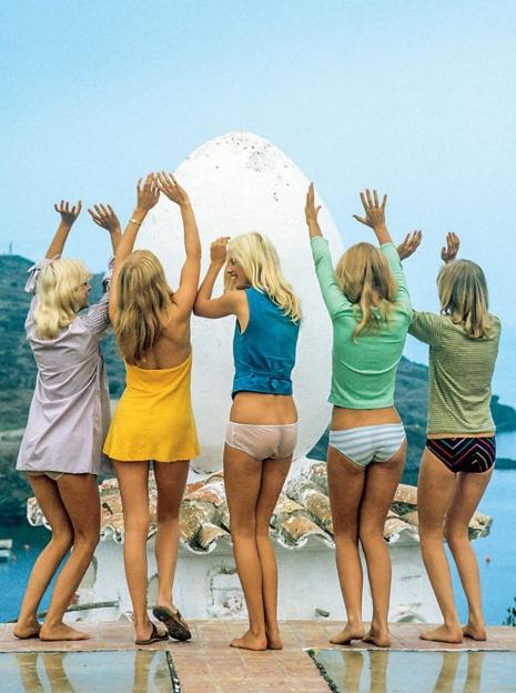 Na zdjęciu widzimy 5 modelek ubrane w koszulki i majtki, stoją tyłem do fotografa a przodem do dużego, kurzego jaja i mają podniesione ręce ku niebu.