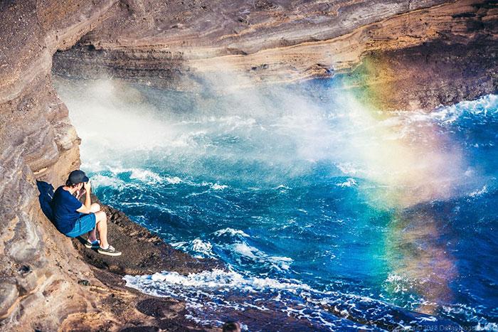 Na zdjęciu znajduje się mężczyzna siedzoący na skraju skały obok wodospadu