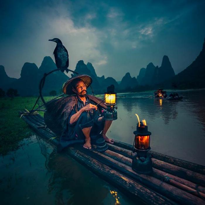 Na zdjęciu znajduje się mężczyzna w kapeluszu siedzący na tratwie i trzymający zapaloną lampę