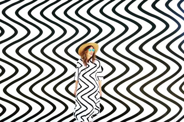 Artystka stoi na tle tapety w czarne mazgaje. Ma na sobie sukienkę w tym samym wzorze.