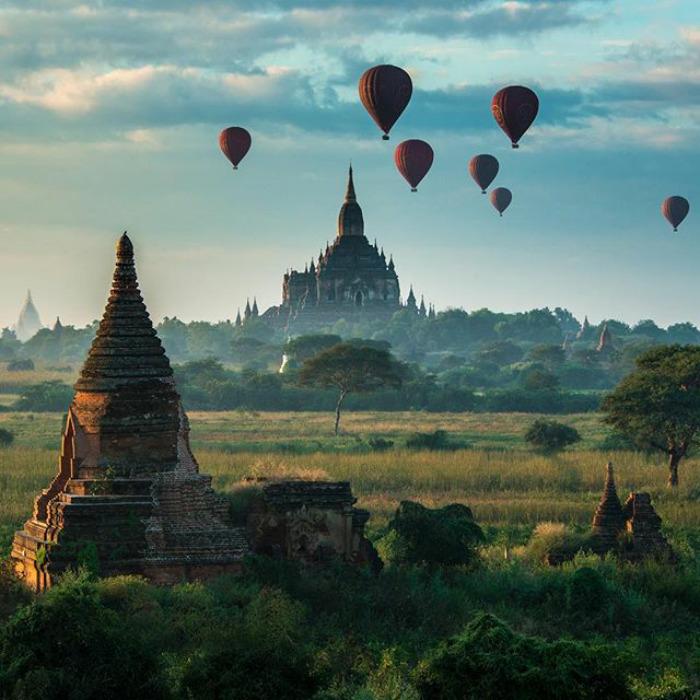 Na zdjęciu znajdują się zabytkowe budynki z Birmy, które są tłem dla wznoszących się w niebo balonów