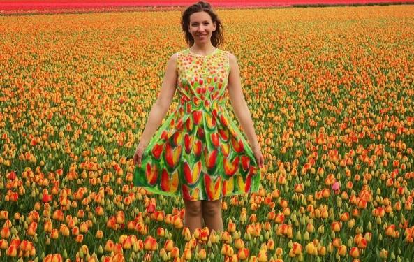 Artystka stoi na polu pełnym pomarańczowych tulipanów, ma na sobie sukienkę w ten sam motyw.