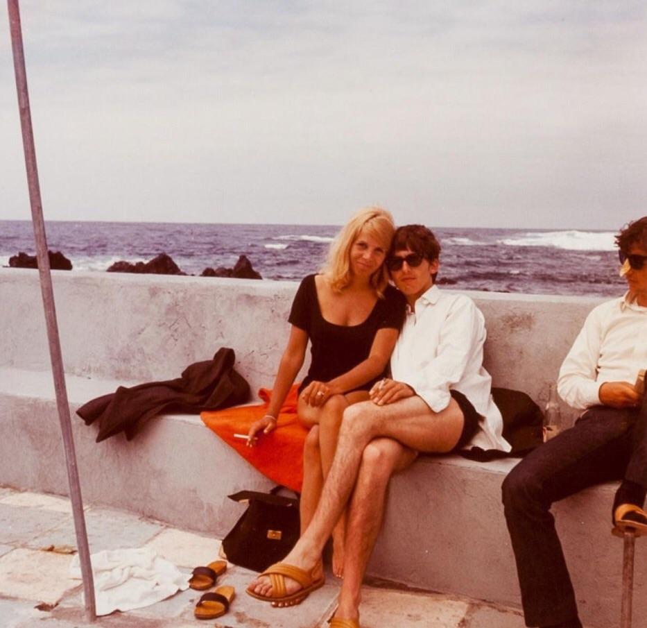 Na zdjęciu widzimy muzyka i kobietę, przytulonych do siebie. Siedzą na bulwarze.Na zdjęciu widzimy kawałek drugiego muzyka.