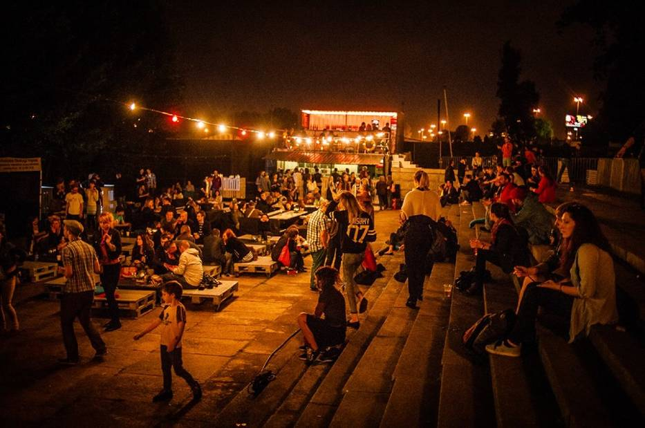 """Zdjęcie przedstawia bulwar nad wisłą wieczorem. Ludzie siedzą na schodkach przy rzece, w oddali widać scenę klubu """"Cud nad Wisłą""""."""