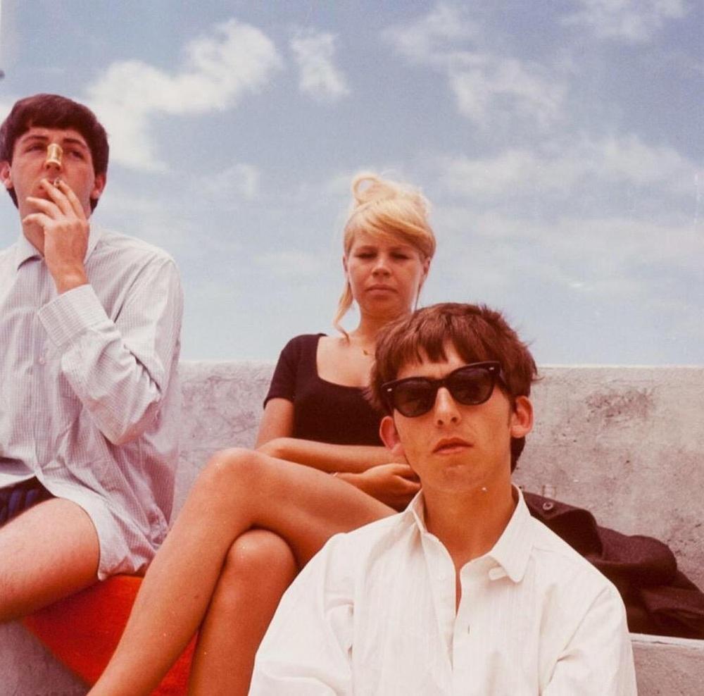 Na zdjęciu widzimy dwóch muzyków i blondynkę. Jeden muzyk ma ciemne okulary, zaś drugi pali papierosa.