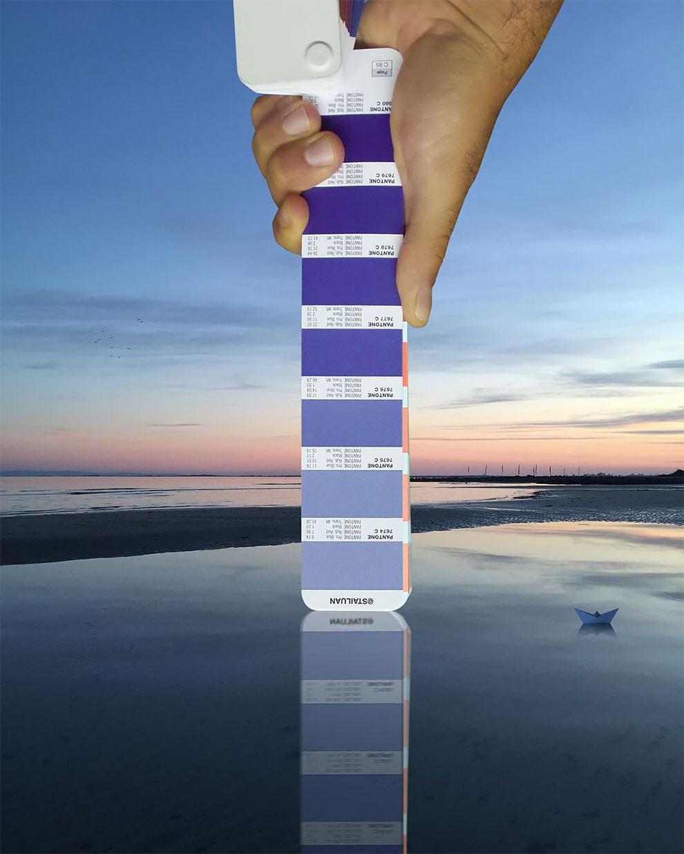 Ręka trzymająca próbnik niebieskich kolorów Pantone na tle zachodu słońca