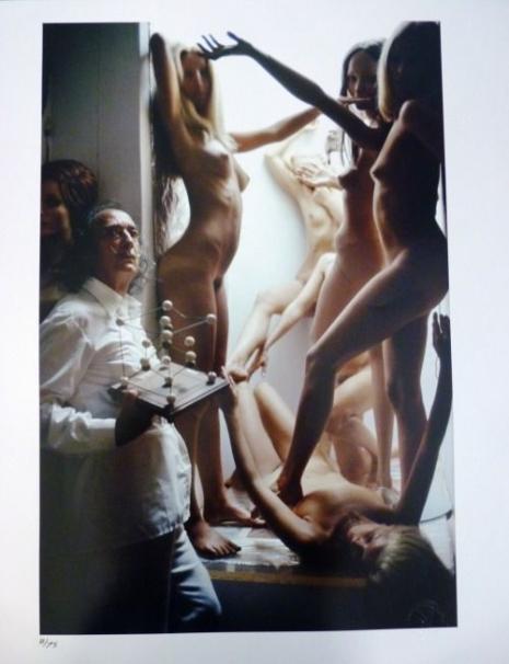 Na zdjęciu widzimy Salavdora Dali, a za nim soją nagie modelki które opierają się o framugę drzwi.