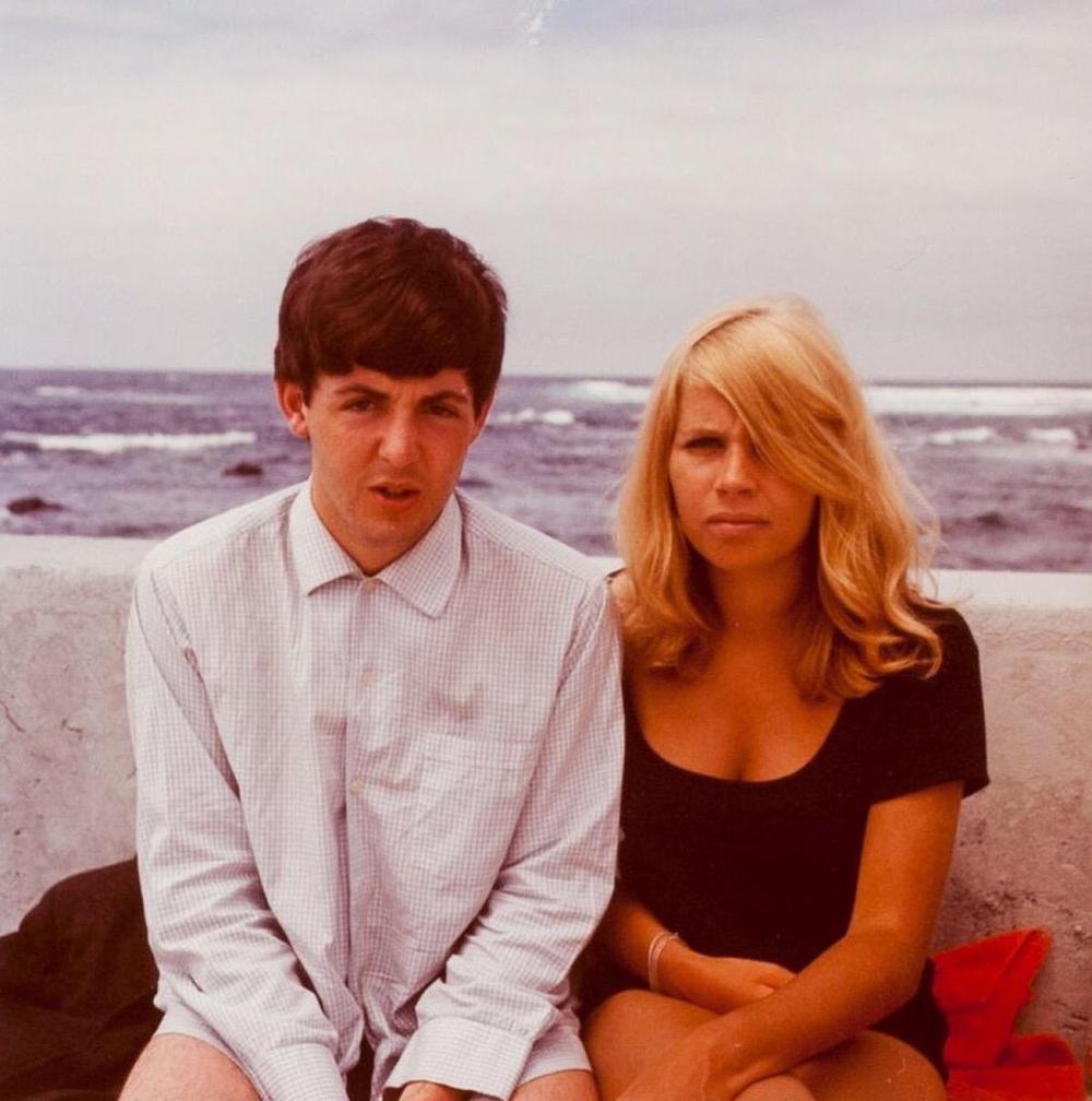 Na zdjęciu widzimy muzyka ubranego w białą koszulę i marynarkę białą, obok niego siedzi blondynka w czarnej sukience.