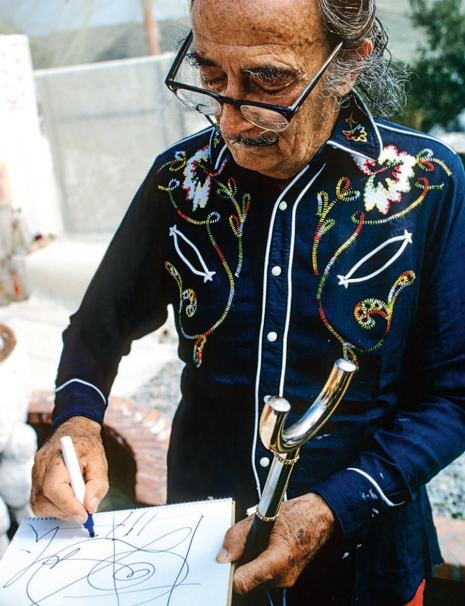 Na zdjęciu widzimy Salvadora Dalego, który ma okulary, i stoi szkicując.
