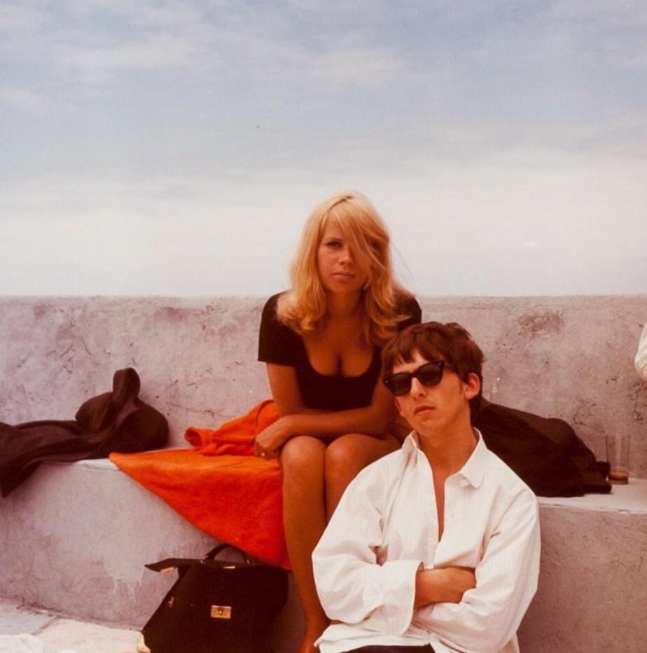Na zdjęciu widzimy muzyka w białej koszuli oraz blondynkę. Oboje siedzą na bulwarze.