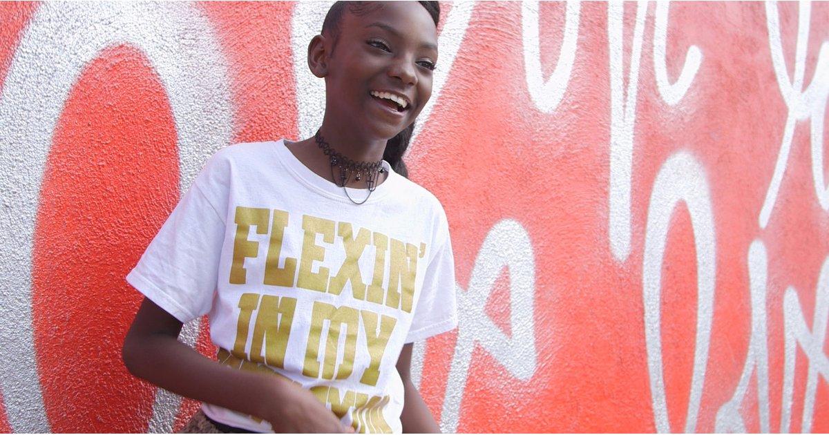 czarnoskora dziewczynka w bialej koszulce ze zlotym napisem na tle czerwonej sciany