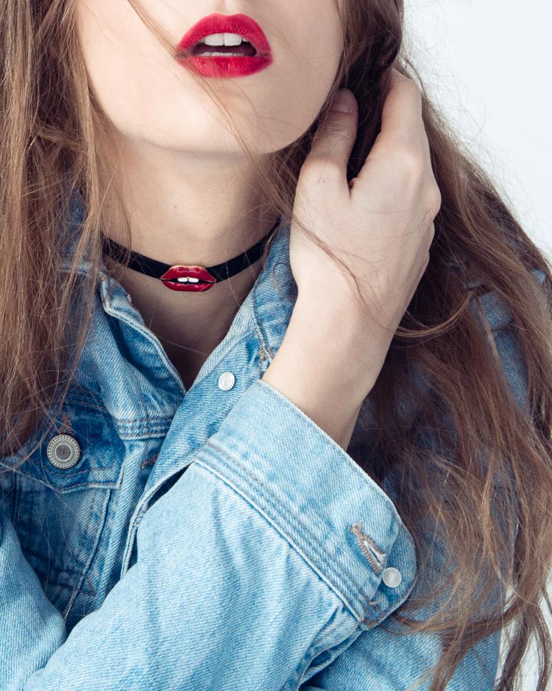 Zbliżenie na rozchylone usta dziewczyny, na której szyi znajduje się chocker i ubrana jest w jeansową kurtkę