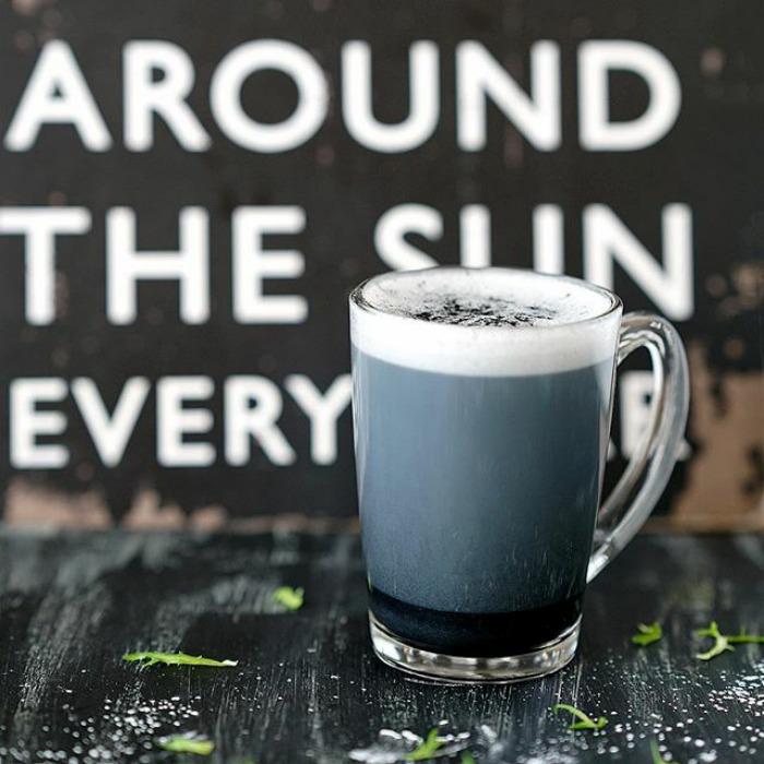 Na zdjęciu widnieje kubek z kawą latte, która jest koloru ciemnego. Kubek stoi na stole, a w tle widać ozdobne napisy na ścianie