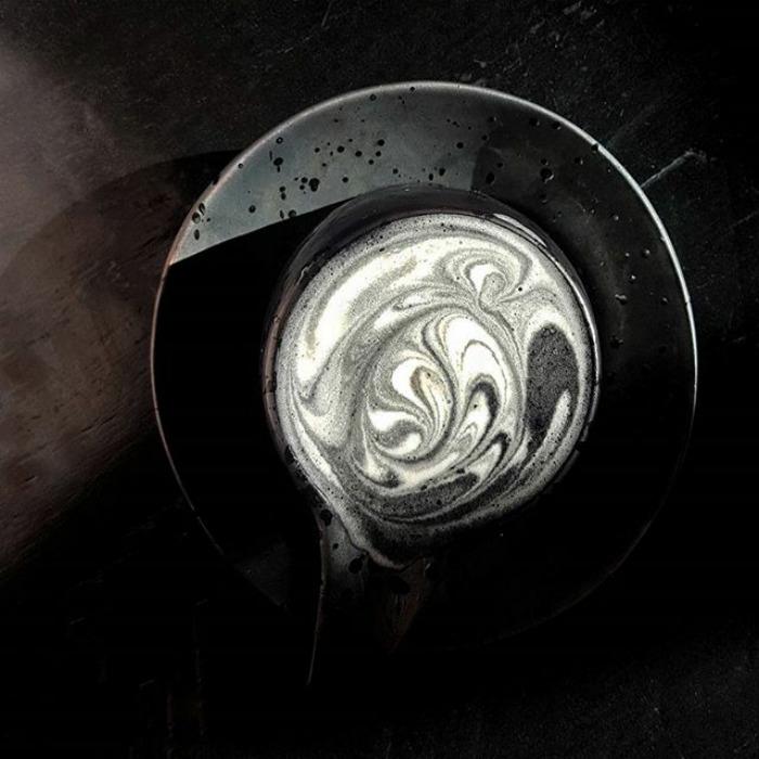 Zdjęcie jest lekko przyciemnione i na pierwszym planie jest ciemne latte w czarnej filiżance i na czarnym talerzyku