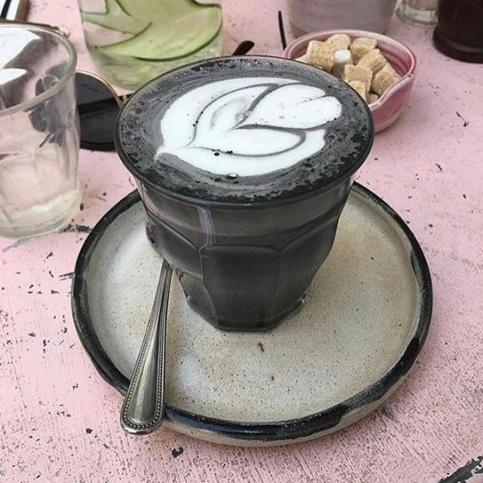 Na zdjęciu jest ciemna kawa latte w czarnym kubku, w oddali stoją inne kubki.
