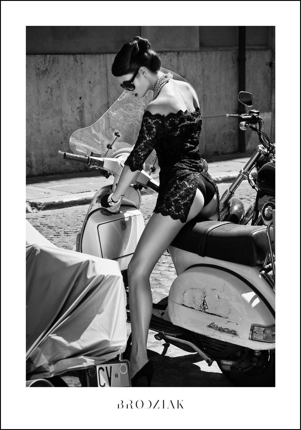 Czarno-białe zdjęcie kobiety siedzącej na skuterze